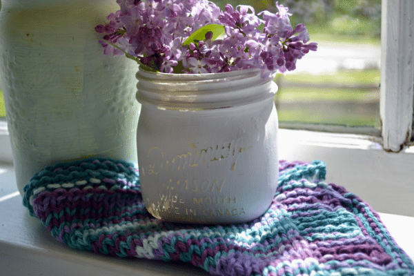 Vintage white chalk painted mason jar with purple lilac followers sitting on a window sill on the framed zig zag knit dishcloth pattern cloth
