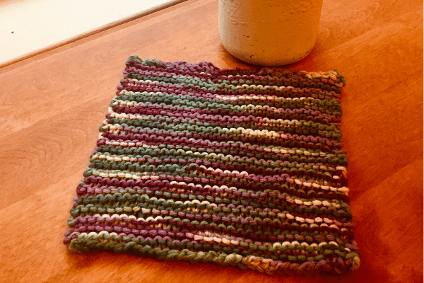garter stitch knit dishcloth pattern flat lay on kitchen table with mason jar in background