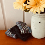 knitted dishcloth pile on counter next to vase of flowers