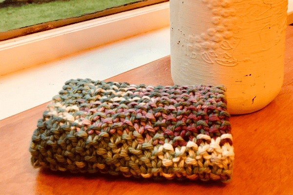 seed stitch knit dishcloth pattern folded in thirds sitting on kitchen table with mason jar in background